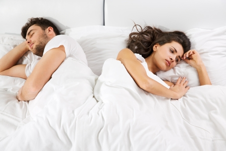 quarrel: Upset young couple having disagreement lying side by side in bed facing in opposite directions