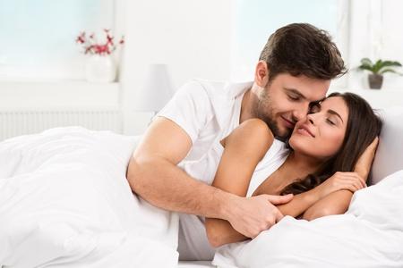 enamorados en la cama: Joven pareja heterosexual desnuda acostada en la cama en el dormitorio Foto de archivo