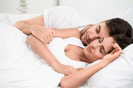 enamorados en la cama: Pareja de adultos jóvenes que duermen en la cama en el dormitorio Foto de archivo