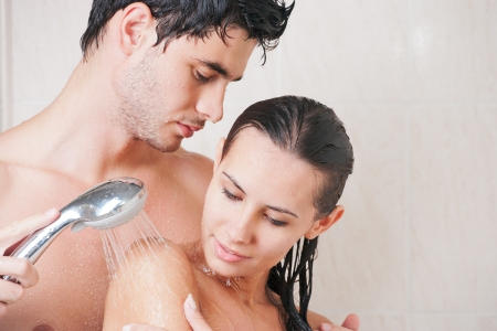 Young beautiful couple washing in the shower photo