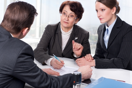 notary: Agent  or notary public  signing documents with with senior woman and her daughter