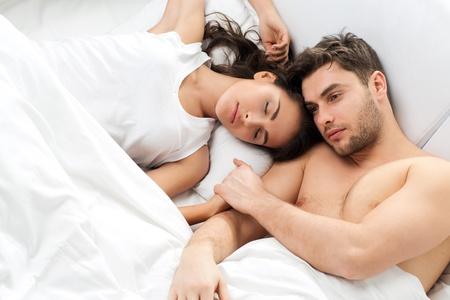 Young adult heterosexual couple lying on bed in bedroom photo