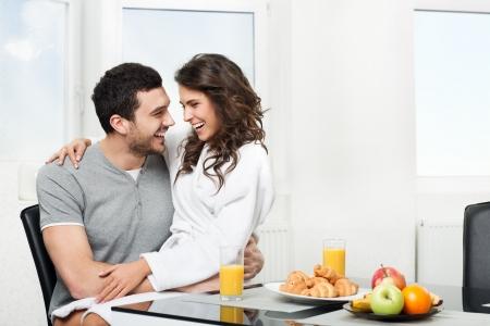 朝食のテーブルを持っている美しいカップル、彼氏の手に座っている女の子