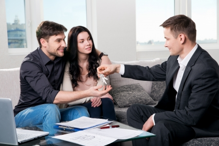 buying a home: Happy couple with real estate agent