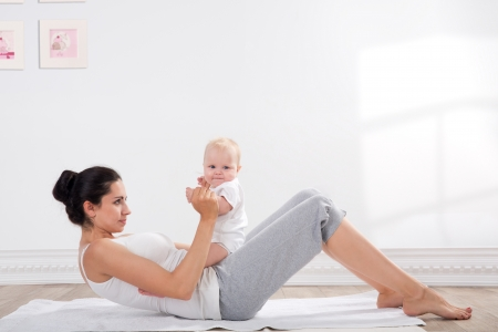 aerobic exercise: young mother does physical fitness exercises together with her baby