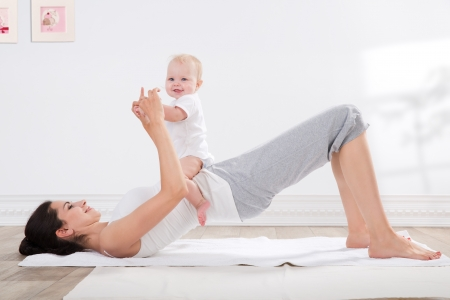 indoors: young mother does physical fitness exercises together with her baby
