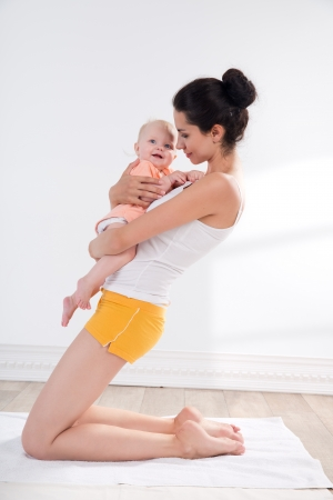 strenuous: young mother does physical yoga exercises together with her baby