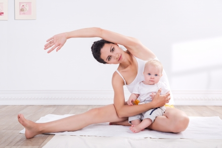 yoga mat: young mother does physical yoga exercises together with her baby