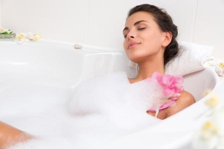 baÑo: joven mujer hermosa morena toma un ba?o de burbujas Foto de archivo