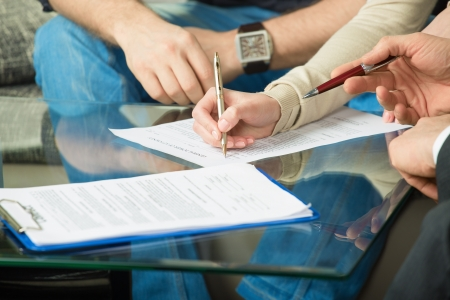 Handen van mensen ondertekende het document, zittend aan de balie Stockfoto