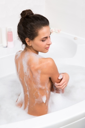 young beautiful brunette woman takes bubble bath, rear view photo