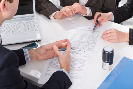 Three people sitting at a table signing documents, hands close-up Standard-Bild