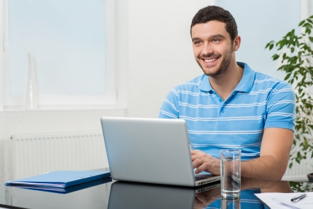 幸せな若い実業家のラップトップのテーブルに座って