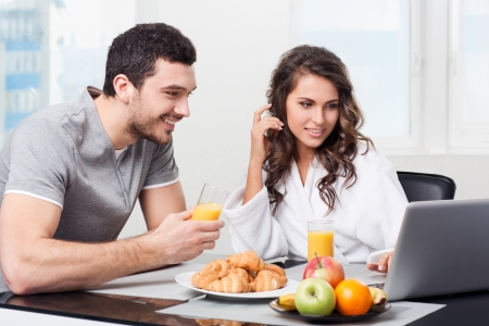 young lovers: young beautiful couple having breakfast with a laptop