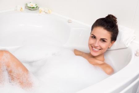 young beautiful brunette woman takes bubble bath