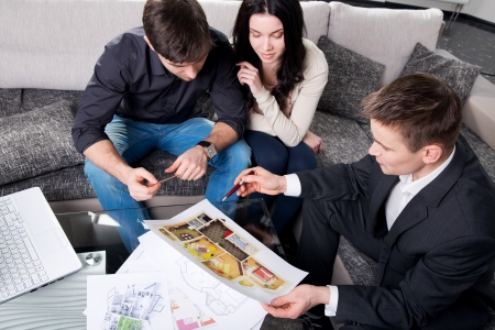 designer working: couple is considering the future design of the apartment with a designer, top view