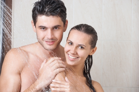 mojado: Pareja joven que se lava la cabeza en la ducha