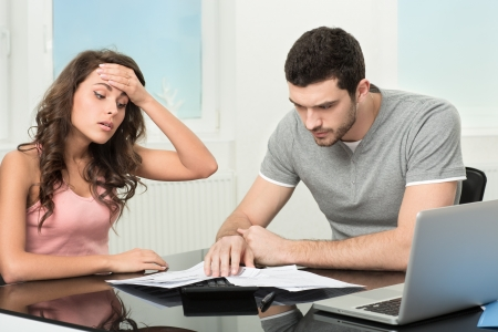 Couple, Man angry and upset after looking at credit card statement  photo