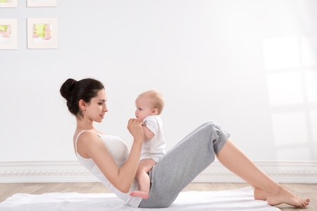 young mother does physical fitness exercises together with her baby Stock Photo - 53034586