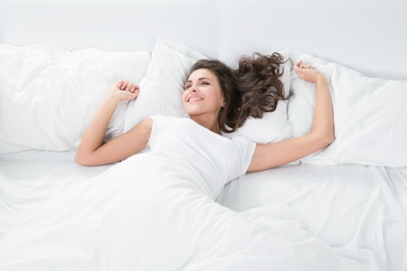 young woman sleeping on the white linen in bed at home, top view Standard-Bild