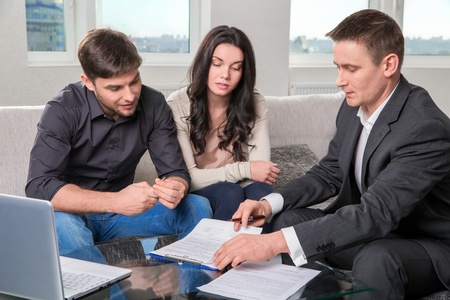 financial agreement: couple consults with agent, signing paperwork Stock Photo