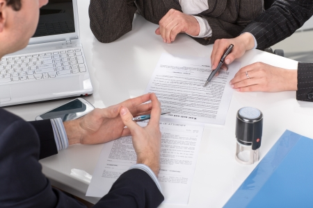 Three people sitting at a table signing documents, hands close-up Stock Photo