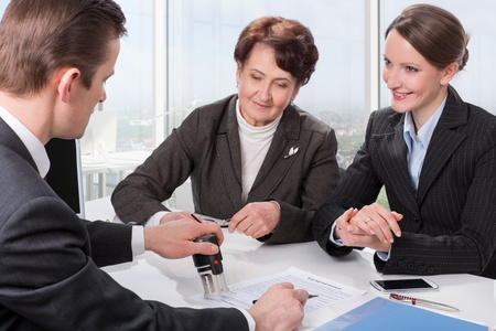 notary: Agent (or notary public) signing documents with senior woman and her daughter