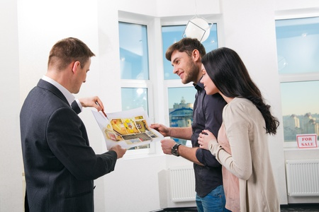 designer: couple is considering the future design of the apartment with a designer