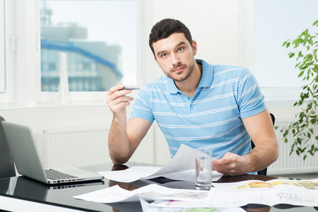 oppressed: handsome young interior designer or architect at workplace