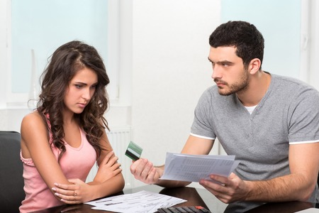 over paying: Couple, Man angry and upset after looking at credit card statement.