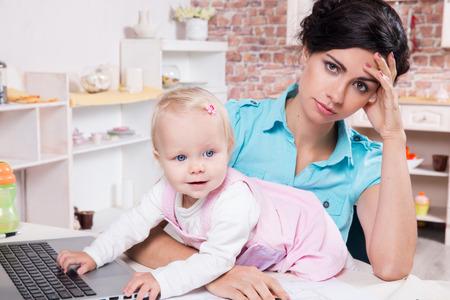 madre trabajando: Joven mujer de negocios con ordenador portátil y su bebé