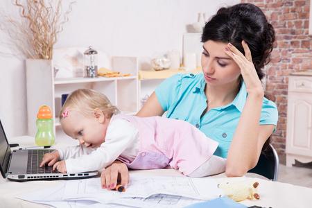 Jonge zakenvrouw met laptop en haar babymeisje