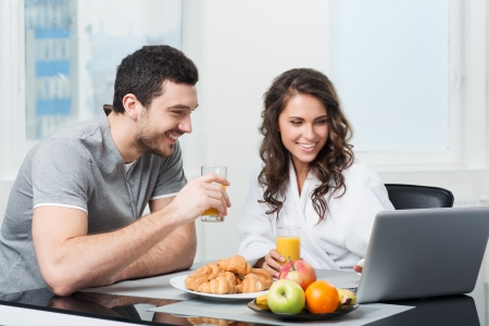young beautiful couple having breakfast with a laptop photo