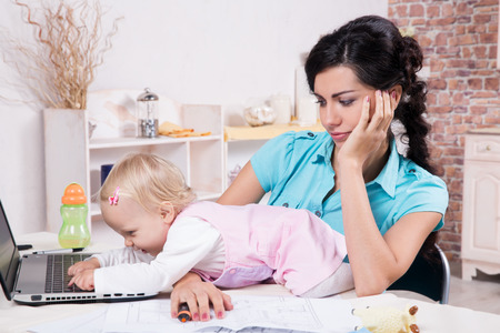 baby with mother: Young business woman with laptop and her baby girl