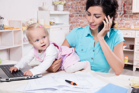 Young business woman with baby in the kitchen working with laptop, speaks by phone