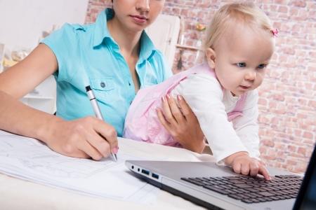mamans: femme d'affaires avec le b�b� dans la cuisine de travail avec un ordinateur portable