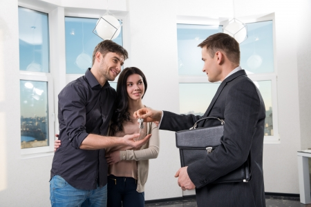 real estate agent gives the couple the keys to a new apartment Stock Photo