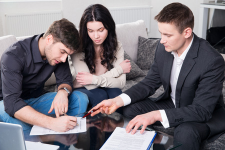 financial planning married: couple consults with agent, signing paperwork Stock Photo