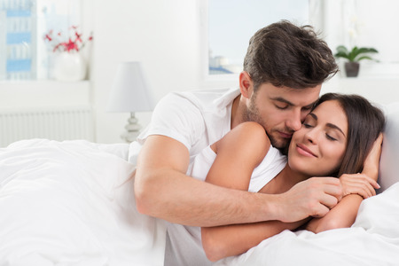 romantic couples: Young adult heterosexual couple lying on bed in bedroom