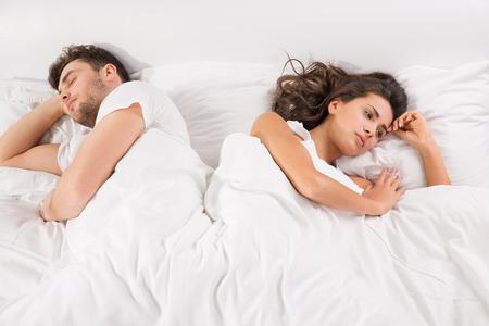 側で反対方向に直面してベッドに横たわっての不一致を持っている若いカップルを混乱させる