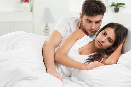 beds: portrait of unhappy young heterosexual couple in bedroom