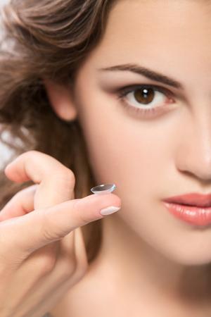 カメラを探している若い女性の指にコンタクト レンズ