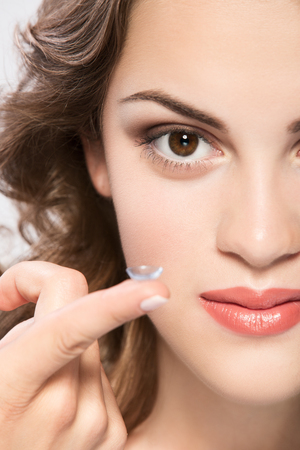 eye lens: contact lens on finger of young woman looking on camera