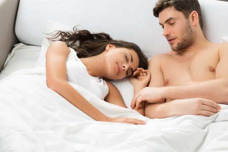 wife and husband: Young adult heterosexual couple lying on bed in bedroom