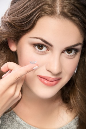 contact lens: contact lens on finger of young woman looking on camera
