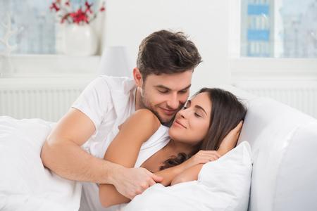 jovenes felices: adulto joven pareja heterosexual acostado en la cama en el dormitorio