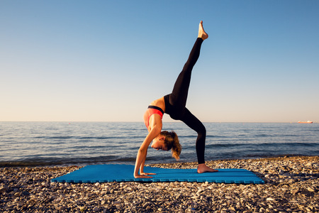 yoga sunset: Woman stretching in yoga exercise fitness training at coastline at sunset Stock Photo