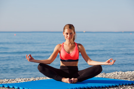 Woman stretching in yoga exercise fitness training at coastline at sunset photo
