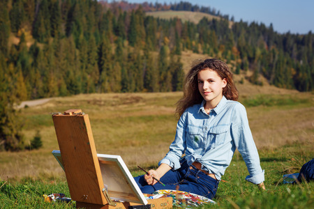 Young painter at work in the mountains with palette photo