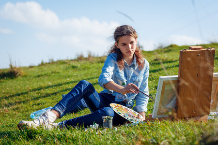 painter girl: Young painter at work in the mountains with palette
